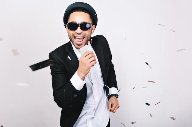 Entertainment, het vieren van karaokepartij van opgewonden knappe jongen in zwarte zonnebril met plezier. modieuze uitstraling, zingen, muziek, genieten, positiviteit uitdrukken, geluk.