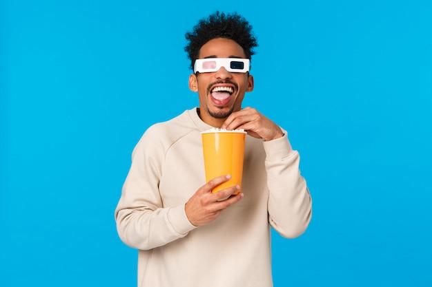 Entertainment, lifestyle en mensen concept. zorgeloos gelukkig en ontspannen afro-amerikaanse man in witte trui, kijken naar grappige interessante film, popcron eten en het dragen van een 3d-bril, blauwe achtergrond
