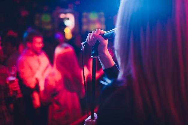Entertianment op een bruiloft. een zangeres communiceert met de menigte terwijl een man een akoestische gitaar speelt.