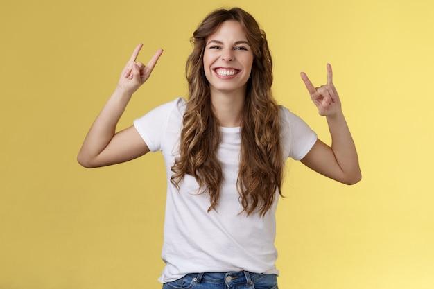 Enthousiast charismatisch gelukkig meisje met plezier geniet van geweldige muziek show rock-n-roll gebaar grijnzend opgewonden als heavy metal dansen vrolijk positief staand vermaakt gele achtergrond