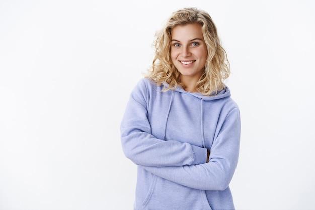 Enthousiast en teder schattig blond meisje met blauwe ogen en kort kapsel in paarse stijlvolle hoodie hand in hand gekruist over borst om op te warmen in koude kamer glimlachend blij en zachtaardig naar de camera