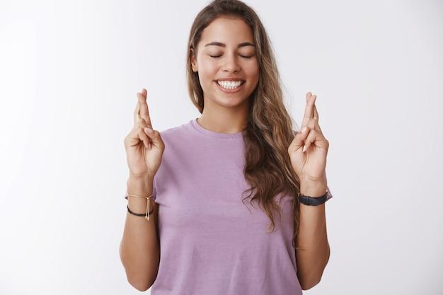 Enthousiast gelukkig hoopvol kaukasisch meisje student kruis vingers geluk ogen sluiten glimlachen bidden wensen maken vooruitlopend op goede resultaten, optimistische houding, staande witte muur