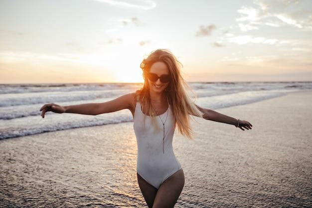 Enthousiast kaukasisch meisje dat langs de oceaankust loopt en lacht. openluchtportret van blije vrouw in wit zwempak die van de zomervakantie genieten in exotische toevlucht.