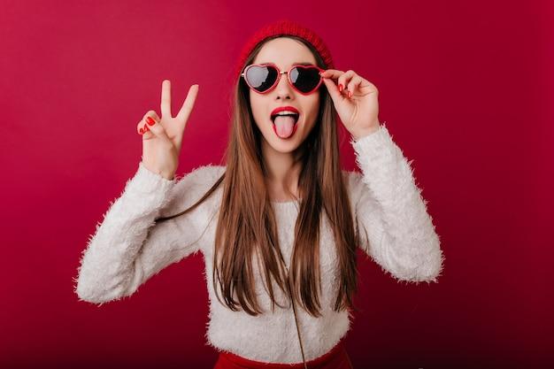 Enthousiast langharig meisje draagt coole zonnebril poseren met vredesteken