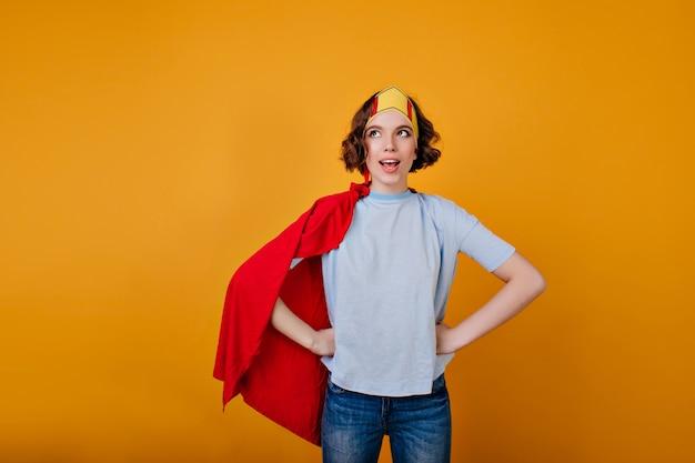 Enthousiast meisje met krullend kapsel poseren in rode mantel