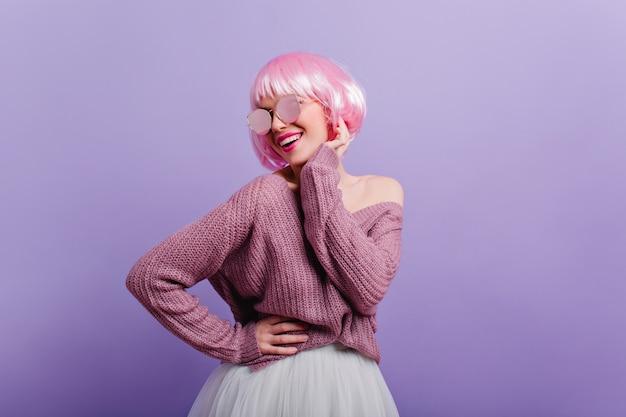 Enthousiast vrouwelijk model in trui en rok dansen en lachen. geïnspireerde jonge vrouw met roze haar geïsoleerd op paarse muur.