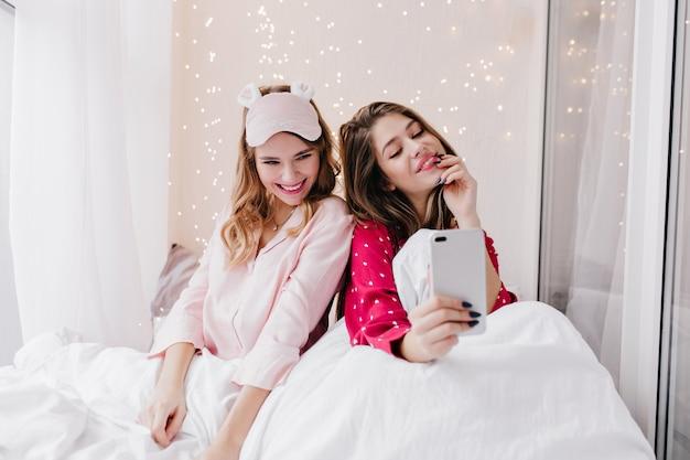 Enthousiast wit meisje in slaapmasker poseren in bed. schattige vrouw met behulp van telefoon voor selfie in slaapkamer.