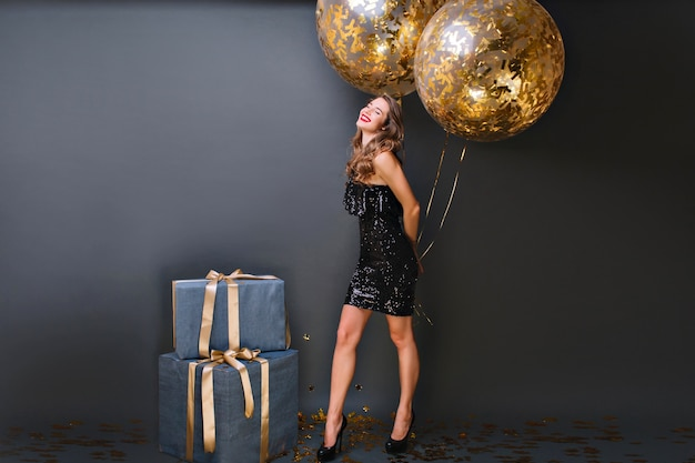 Enthousiast wit meisje met fonkelende heliumballons die van verjaardagsfotoshoot genieten. schattig vrouwelijk model in zwarte jurk poseren met grote huidige dozen en glimlachen.