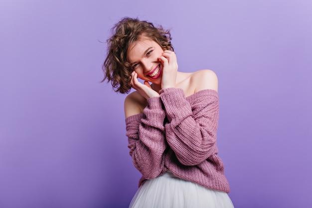 Enthousiast wit meisje speels poseren in outfit. indoor portret van geïnspireerde kortharige vrouw geïsoleerd op paarse muur.