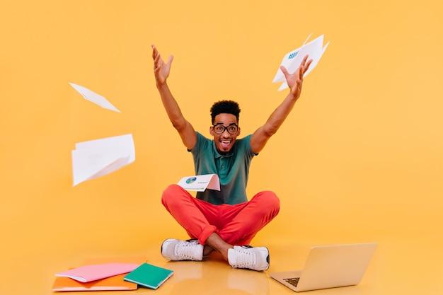 Enthousiaste afrikaanse student in rode broek die tijdens studie voor de gek houdt. lachende mannelijke freelancer handen zwaaien.