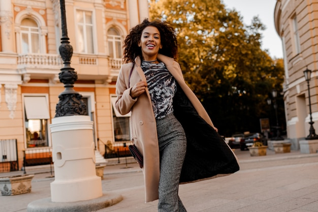 Enthousiaste afrikaanse vrouw in elegante casual outfit hardlopen en plezier maken.