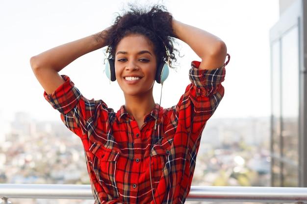 Enthousiaste amerikaanse vrouw met donkere huid poseren met koptelefoon op het dak. stedelijk landschap achtergrond.