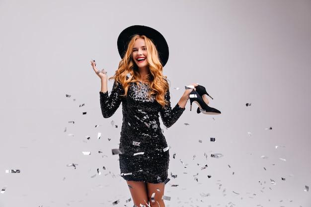 Enthousiaste blanke vrouw in trendy hoed poseren met confetti. schot van lachen romantische dame in glanzende zwarte jurk.