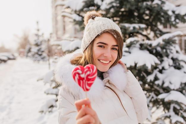 Enthousiaste blanke vrouw met hart lolly tijdens winter fotoshoot. blije vrouw draagt een gebreide muts en een witte jas die poseren met zoete snoepjes tijdens het werken in een besneeuwd park.