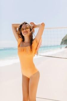 Enthousiaste bruinharige vrouw met slank lichaam poseren aan zandstrand. buitenfoto van vrij kaukasisch meisje dat van zonnig weer geniet bij exotisch eiland.