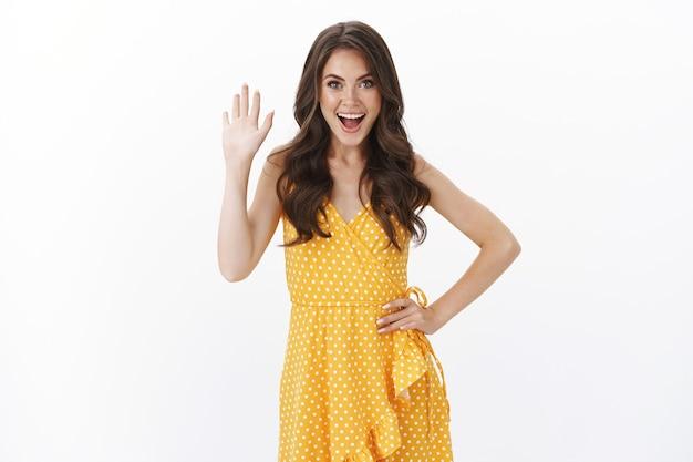 Enthousiaste charismatische mooie brunette vrouw in gele stijlvolle jurk, zwaaiende hand zeggen hallo glimlachend vriendelijk vrolijk blij om vriend, groetende persoon, witte muur