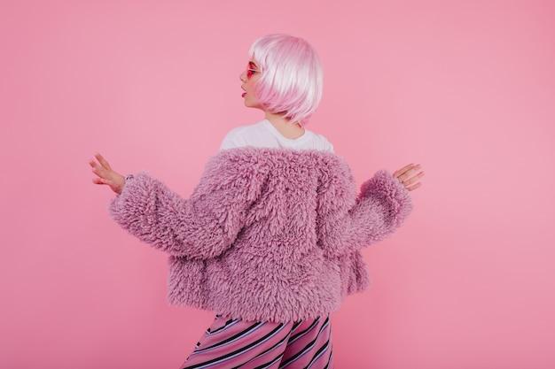 Enthousiaste dame in bontjasje en trendy glanzende peruke-dans. binnenfoto van achterkant van blithesome vrouw in periwig geïsoleerd op pastel muur
