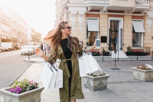 Enthousiaste donkerharige vrouw draagt trendy jas met smartphone en papieren zakken