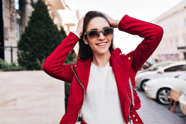 Enthousiaste donkerharige vrouw in zonnebril lachen in zonnige dag op straat