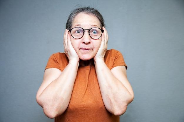 Enthousiaste en verrast oudere vrouw in bruin t-shirt op grijze muur