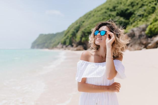 Enthousiaste europese vrouw die in de zomeruitrusting hemel bekijkt. outdoor portret van lachende mooie dame poseren tijdens rust op het strand.