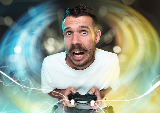 Enthousiaste gamer. vrolijke jonge man met een video game controller vol emoties geïsoleerd op een kleurrijke achtergrond. kaukasische speler. gek worden. heeft het slechtste team in videogames.