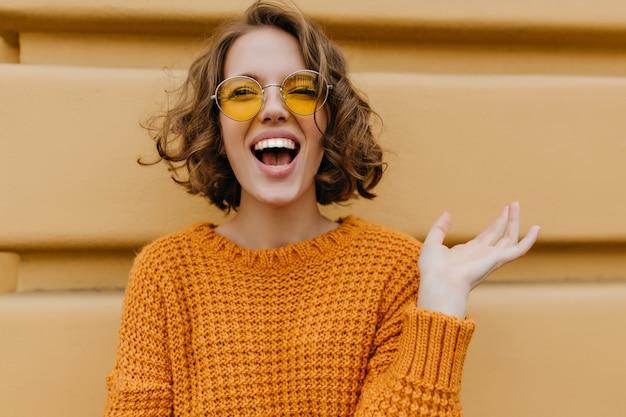 Enthousiaste glimlachende vrouw met glanzende krullen die voor oude muur stellen