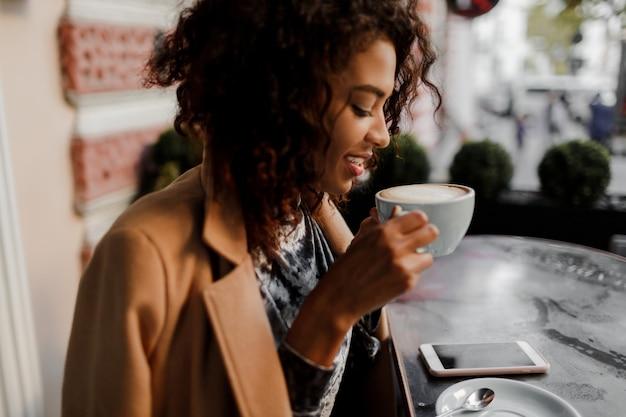 Enthousiaste hipster donkere vrouw met afro kapsel controleren van haar nieuwsfeed