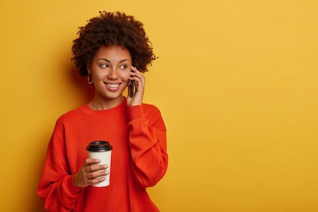 Enthousiaste jonge afro-meid voert telefoongesprek, spreekt met vriend en hoort grappige grappen, gekleed in vrijetijdskleding