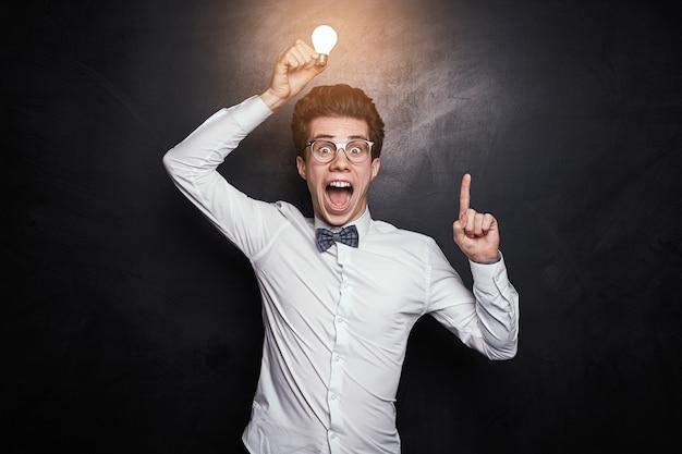 Enthousiaste jonge mannelijke nerd in vlinderdas en bril die gloeiende gloeilamp boven het hoofd houdt en met wijsvinger omhoog gebaart alsof ze een briljant idee hebben terwijl ze tegen schoolbord staan