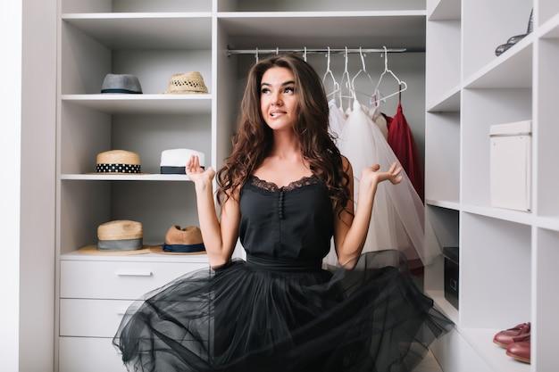 Enthousiaste jonge vrouw in kleedkamer, garderobe en denken, heeft contemplatieve blik. haar prachtige zwarte jurk zweeft in de lucht. ze heeft lang krullend bruin haar.