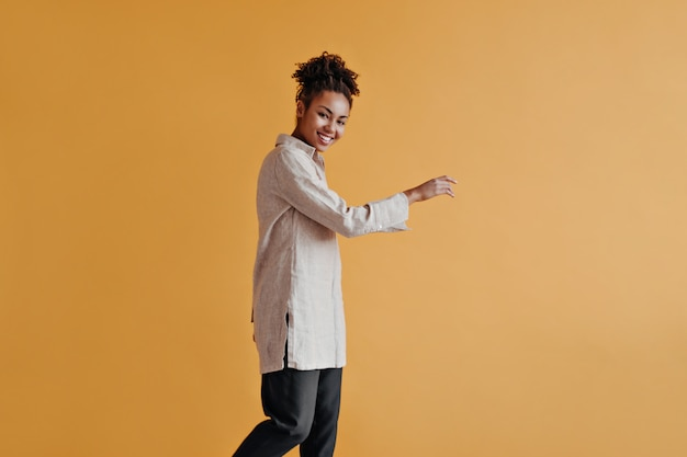 Enthousiaste jonge vrouw poseren in lang shirt