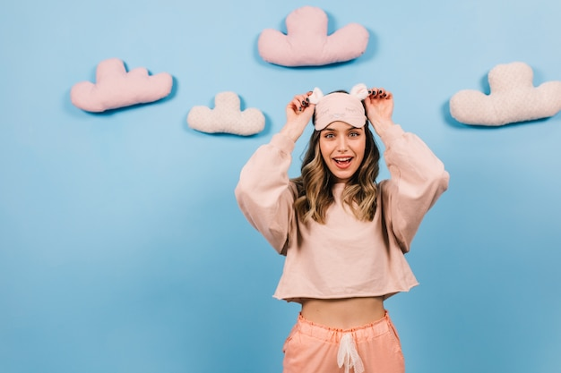 Enthousiaste jonge vrouw poseren in pyjama en slaapmasker