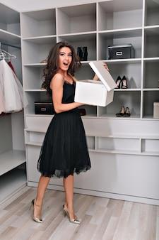 Enthousiaste jonge vrouw staat in een stijlvolle kledingkast met een open doos in zijn handen. ze is gekleed in een zwarte jurk en zilveren schoenen. wauw emoties.