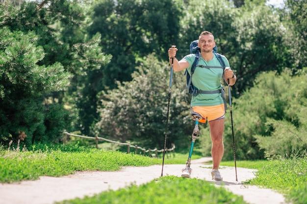 Enthousiaste jongeman die nordic walking probeert terwijl hij ondanks moeilijkheden actief blijft