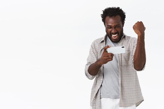 Enthousiaste knappe gelukkige afro-amerikaanse man, die smartphone horizontaal houdt