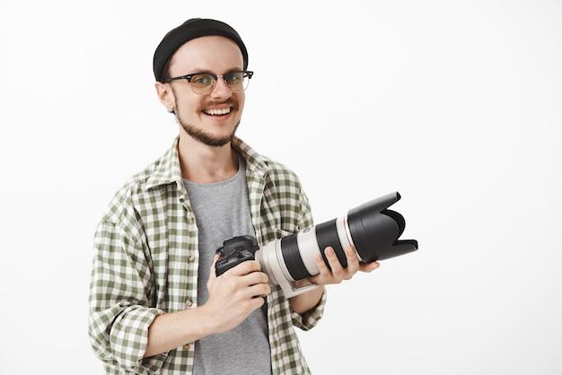 Enthousiaste knappe volwassen man in glazen en zwarte muts met professionele camera en lachend van vreugde als journalist of fotograaf