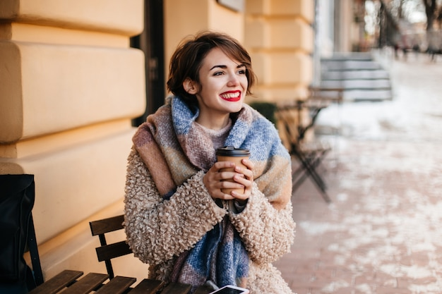 Enthousiaste kortharige vrouw die koffie drinkt in de stad