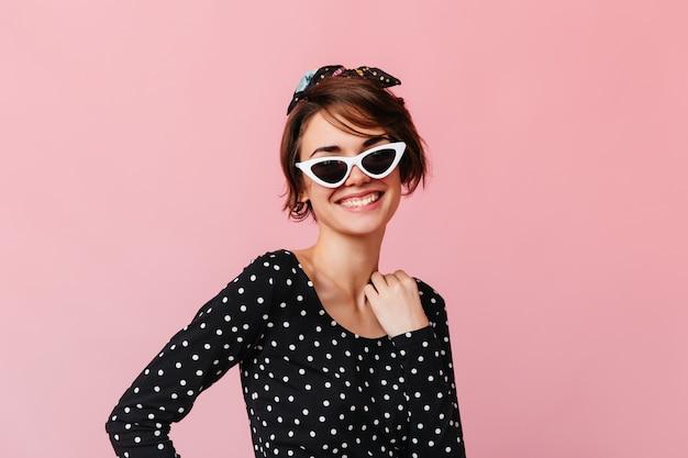 Enthousiaste kortharige vrouw poseren in zonnebril
