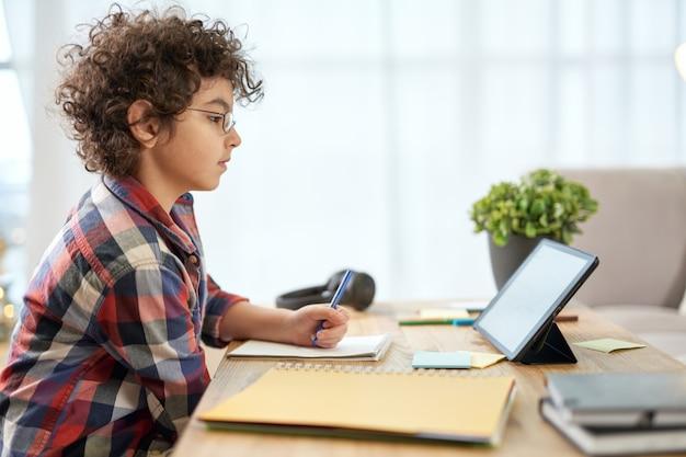 Enthousiaste latijns-schooljongen met een bril die aantekeningen maakt, online les heeft met behulp van digitale tablet terwijl hij thuis studeert. online onderwijs, technologie, thuisonderwijs. zijaanzicht