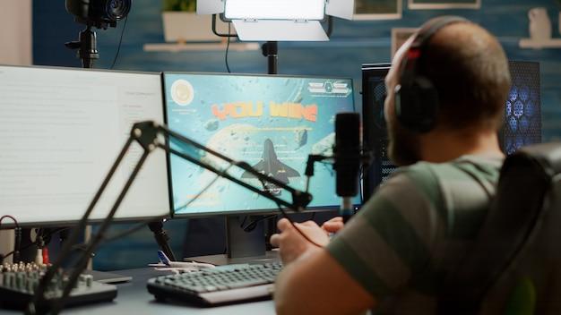 Enthousiaste man gamer streamer wining space shooter videogames met joystick spelen op professioneel rgb-toetsenbord en praten op stream-chat. pro cyber met microfoon in gamingtoernooi