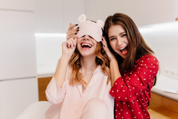 Enthousiaste meisjes in knusse pyjama's die wachten op het ontbijt. indoor portret van charmante europese dames genieten van vrije tijd in de ochtend.