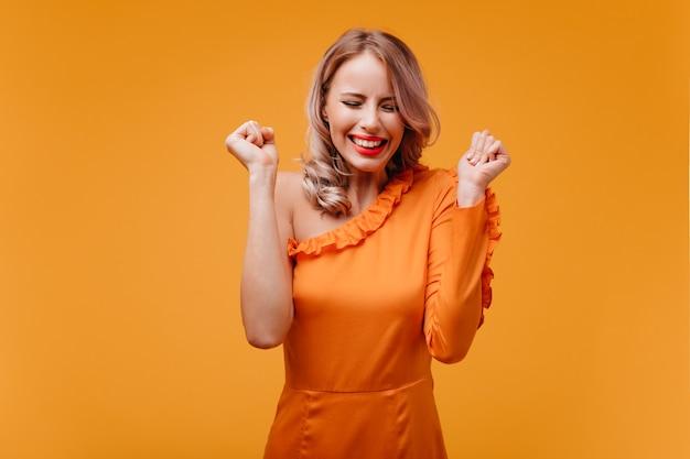 Enthousiaste mooie vrouw lachend met gesloten ogen op gele muur