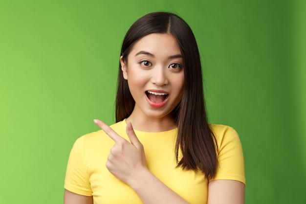 Enthousiaste onder de indruk schattige aziatische brunette die nieuwe haarverzorgingsproducten beschrijft, geamuseerd en verbaasd...