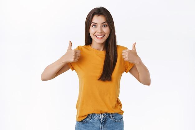 Enthousiaste, opgewonden jonge vrouw vind je idee geweldig, beoordeel een goede film, laat duimen zien lachend blij en geeft haar goedkeuring, ga akkoord met of accepteer iets geweldigs, witte achtergrond
