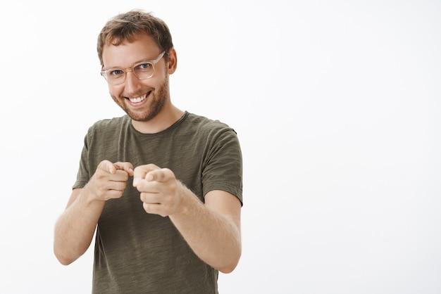 Enthousiaste, vrolijke en zelfverzekerde man met borstelharen in bril en donkergroen t-shirt wijzend met vingerpistoolgebaar alsof hij kandidaat kiest met een brede tevreden glimlach