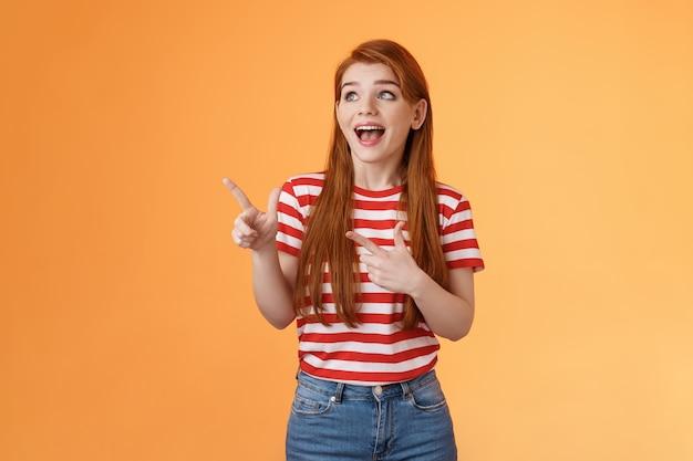 Enthousiaste vrolijke roodharige vrouw levendig lachend lachen vreugdevol genieten van het kijken naar kopie ruimte kijken ...