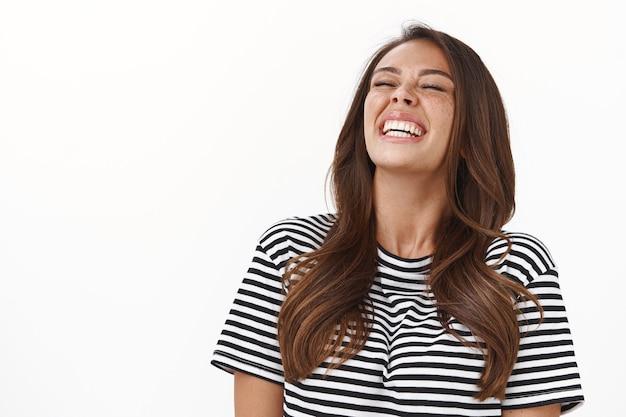 Enthousiaste vrolijke vrouw die vrolijk lacht, plezier heeft, grapjes maakt met vrienden, ogen dicht houdt, hoofd kantelt en breed glimlacht, gestreept t-shirt draagt