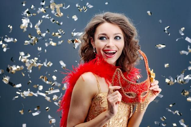 Enthousiaste vrouw die een rood carnaval-masker in haar handen op een feestelijke achtergrond met klatergoud houdt