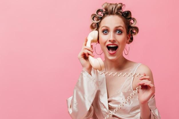 Enthousiaste vrouw in roze gewaad die graag aan de telefoon spreekt en op geïsoleerde muur poseren